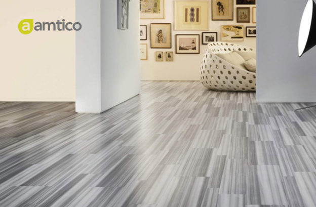 Grey amtico flooring is in focus with a lounge room in the background