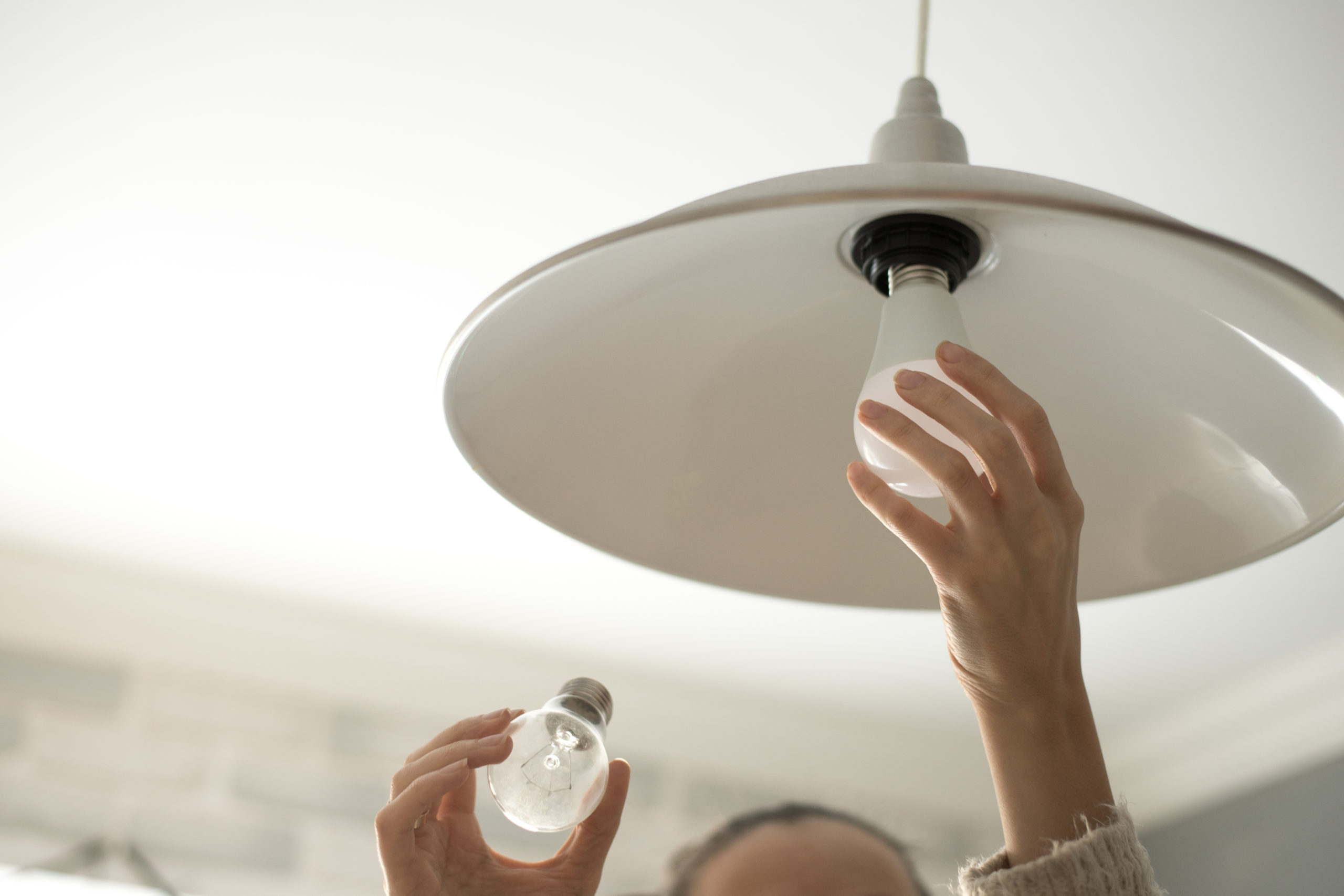 A pair of hands changing a lightbulb because home improvement is a useful way to spend the extra time in the house.